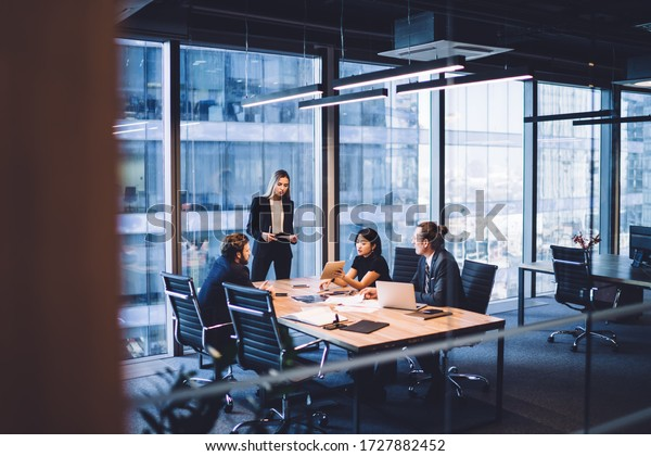 From above of group of diverse colleagues in formal clothing discussing business ideas while gathering at table in modern office and working together
