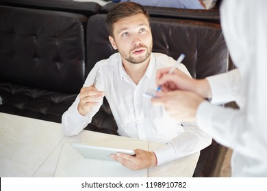 From above of handsome modern businessman at table in cafe with tablet talking to crop waiter and making order
