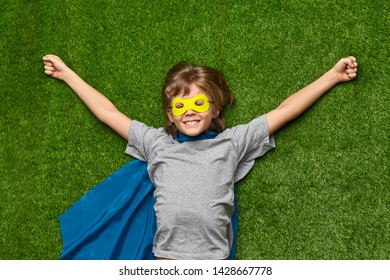 From above happy boy in superhero cape and mask smiling and stretching out arms while lying on green grass after successful rescue operation