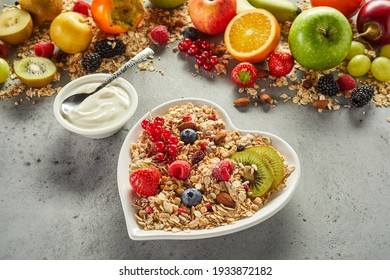 From above heart shaped bowl of healthy muesli placed near fresh yogurt and assorted fruits on gray table in morning