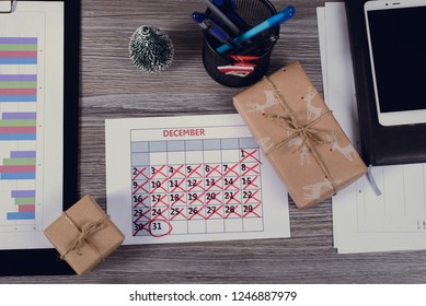 Above high angle close up view photo of calendar with crossed days weeks marked 31 presents near graphs telephone mobile smartphone pen on wooden table