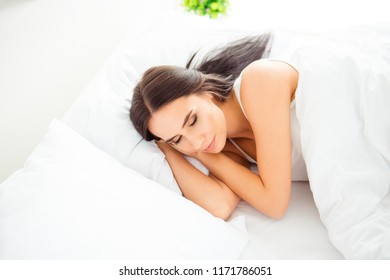 Above high angle view portrait of calm positive dreamy beautiful nice-looking charming woman sleeping in bed in light white interior