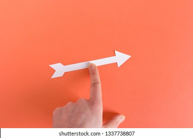 From above image of hand moving white paper arrow in right direction on red background
