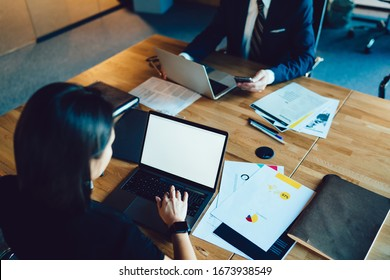 From above image of male and female colleagues sitting at table using digital devices for preparing finance report, businesswoman millennial typing on laptop computer with blank screen checking mail