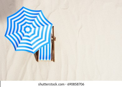 From above of lounge area on beach with striped chair under umbrella.