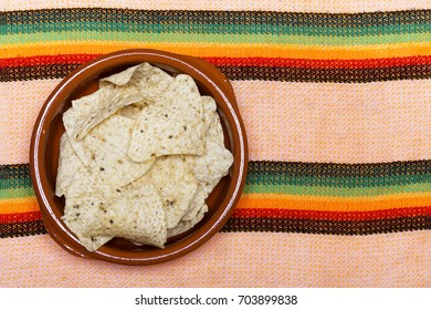 From above nachos snack in bowl on textile background.