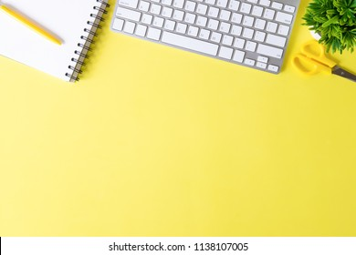 Above Office desk with computer keyboard, notebook paper, pen and plant decoration on yellow background top view mock up.