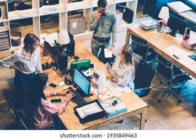 From above of office employee calling on phone discussing project with partners analyzing report of company using computer sitting at table in office looking at each other