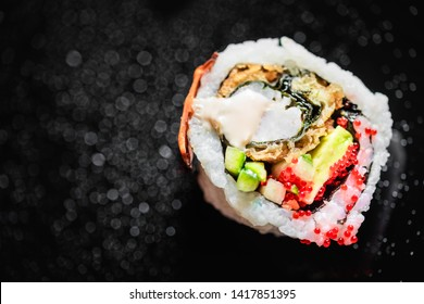 From above of one Uramaki roll with cucumber and avocado and fried seafood filling topped with sauce and tobiko roe