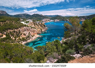 Above panoramic view turquoise bay full of moored luxury yachts motorboats in the Mediterranean Sea, picturesque Cala Blanca Andratx, rocky mountains lush greenery Mallorca, Balearic Islands, Spain