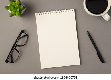 Above photo of notebook green plant glasses cup of coffee and black pen isolated on the grey background