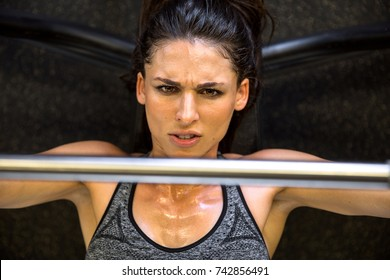 Above point of view female bench pressing with aggressive serious emotional expression