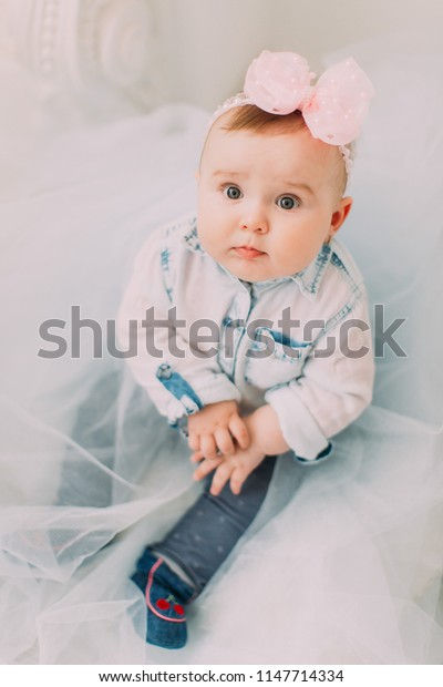 The above portrait of the little baby with the pink bow on the head sitting on the floor with the tulle.