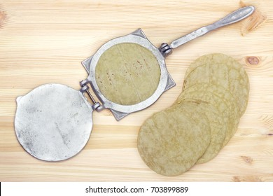 From above press utensil and traditional tortillas placed on wooden background.