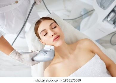 From above of relaxed young female client getting SMAS ultrasound face lifting massage with professional equipment in beauty center - Shutterstock ID 1963175389