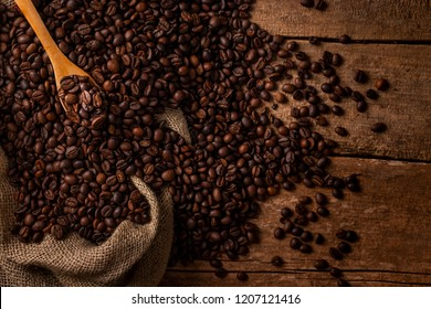 From above of sack spilled fresh coffee beans with wooden spoon