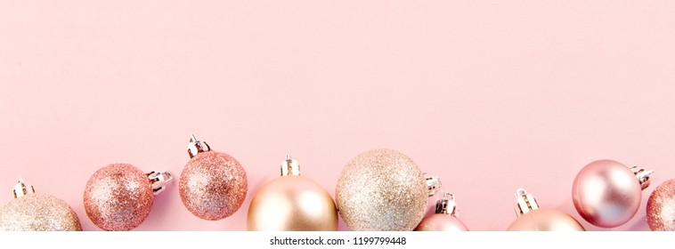 From above shot of bright glittering baubles composed in row on pink background. Christmas concept. Horizontal with place for text
