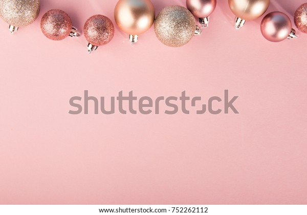 From above shot of bright glittering baubles composed in row on pink background.