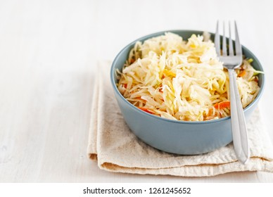 From above shot of ceramic bowl with delectable fermented cabbage and fork standing on napkin on white background
