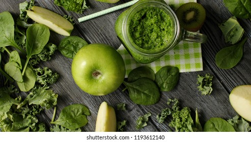 From above shot of green composition with fresh ripe apple and kiwi slices on wooden table with smoothie in jar and fresh greens