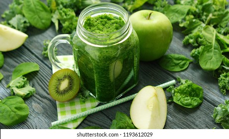 From above shot of green smoothie in glass composed on table with green apple and spinach leaves with kiwi