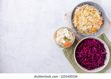 From above shot of jar with pickled cauliflower and bowls with fermented cabbage standing on lumber tabletop