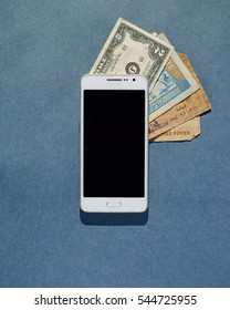From above shot of money lying under smartphone on blue textured background.