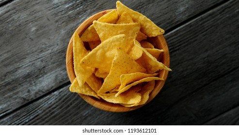 From above shot of round small bowl filled with delicious golden crispy nacho chips and served on gray wooden table