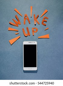 """From above shot of smartphone and word """"wake up"""" of paper pieces on blue textured background."""