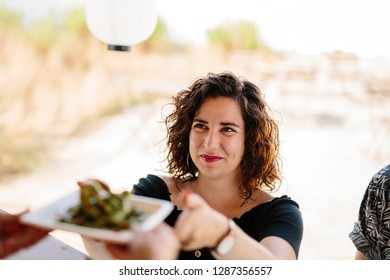 From above shot of smiling woman taking plate with food from vendor in food truck outdoors