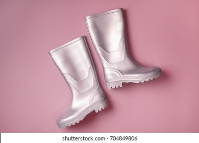 From above shot of trendy silver rain boots on pink background. Top view. Flat lay,