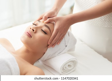 From above shot of unrecognizable woman massaging forehead of beautiful woman while working in spa salon