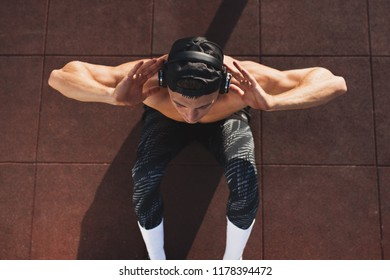 Above shot of young Caucasian sportsman doing sit-ups and listening the music from his headphone. Top view of handsome shirtless male model exercising outdoors.