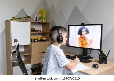 Above shoulder shot of a cute schoolkid watching online video classes sitting on self isolation at home, a smiling female teacher on the screen. E-learning, distance education