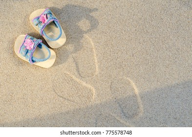From above small child sandals and footprints on sandy beach.