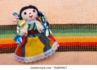 From above small fabric doll girl in colorful dress of Mexico on textile background.