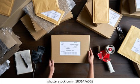 Above table top view of female warehouse worker or seller packing ecommerce shipping order box for dispatching, preparing post courier delivery package, dropshipping shipment service concept.