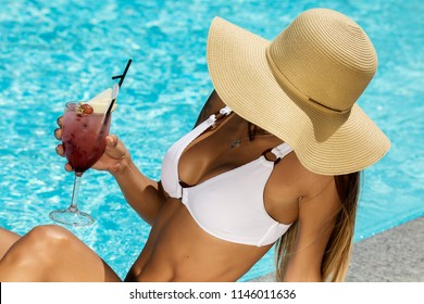 From above of tanned slim woman in bikini and straw hat chilling on edge of pool holding glass with cocktail in sunlight