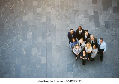 From above team of black and white men and women in formalwear standing in office hall and looking up.