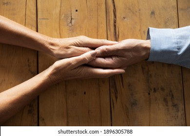 Above top close up compassionate kind middle aged woman holding wrinkled hand of old husband on table, giving psychological help or supporting in difficult life situation, showing love and devotion.