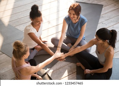 Above top view happy young women wearing sportswear sitting barefoot on yoga mats ready to start training. Attractive girls best friends stacked hands together. Wellness and like-minded people concept