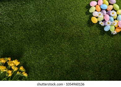 above top view of multi colored painted easter eggs on green grass with springtime daisy flowers and copy space for text
