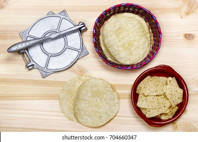 From above tortillas, nachos, and press utensil for cooking on wooden table.