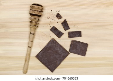 From above traditional wooden Molinillo whisk of Mexico and pieces of mexican chocolate bar on wooden background.
