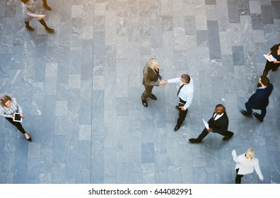 From above two adult business men shaking hands met in office hall with workers walking around.