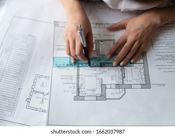 From above unrecognizable designer using ruler and pen to draw line on construction draft during work on project in office