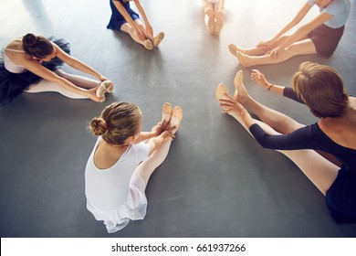 From above unrecognizable little ballerinas with teacher sitting on floor and stretching in ballet class.