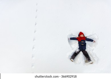 Above view of adorable little girl enjoying beautiful winter day making snow angel