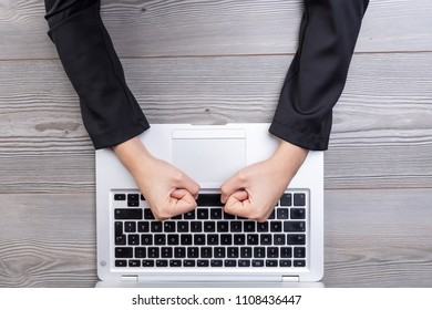 An above view of angry, clenched fists hitting a laptop keyboard on a wooden table background.