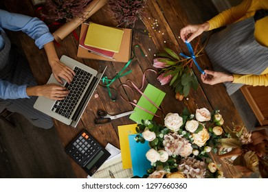 Above view background of shopkeeper using laptop over wooden table in florists shop, copy space